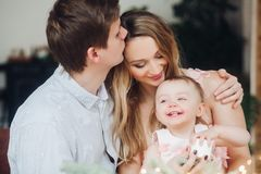 Father kissing beautiful blonde wife, who holding on hands little cute daughter.