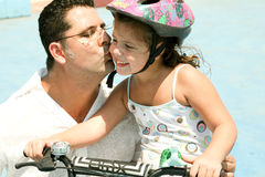 Father kissing daughter. While she rides on bike Stock Photos