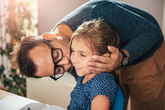Father kissing daughter. While she is doing homework Royalty Free Stock Image