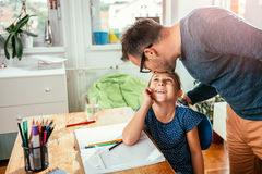 Father kissing daughter. While she is doing homework Royalty Free Stock Photography