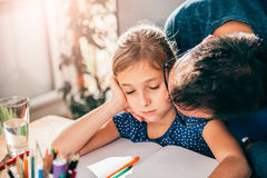 Father kissing daughter. While she is doing homework Stock Photography