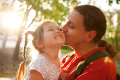 Father kissing daughter. Happy family Royalty Free Stock Photography