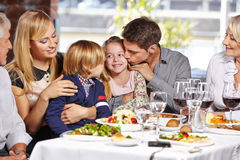 Father kissing daughter. In restaurant while eating out with the family Royalty Free Stock Image