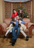 Father kissing daughters on sofa at christmas eve Stock Photography