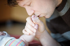 Father kissing foot of newborn baby. Stock Images