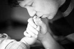 Father kissing foot of newborn baby. Royalty Free Stock Image