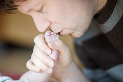 Father kissing foot of newborn baby. Young dad cuddling with new born child at home. Happy parenthood, carefree. Childhood, family, love, tenderness royalty free stock photography