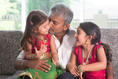 Father kissing her little angel. Happy Indian family at home. Asian father kissing her daughter, sitting on sofa. Parent and children indoor lifestyle Stock Photo