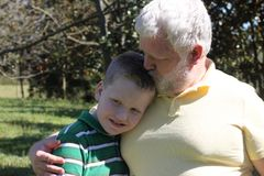 Father Kissing His Autistic Son. On his head in an outdoor setting stock photography
