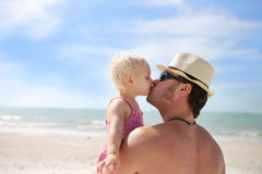 Father Kissing his Baby Daughter on the Beach. A young father is lovingly kissing his one year old baby daughter as they relax on the beach by the ocean Royalty Free Stock Images