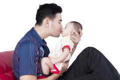 Father kissing his baby on sofa. Young father kissing his adorable baby while sitting on the sofa, isolated on white background Stock Image