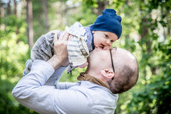 Father kissing his boy in park Stock Photo