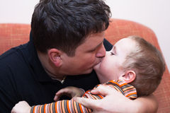 Father kissing his child boy. Closeup of father kissing his child boy Royalty Free Stock Photo