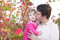 Father kissing his cute daughter in autumn park. Young father kissing his cute baby daughter in an autumn park with beautiful red trees Royalty Free Stock Images