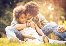 Father kissing his daughter. African American father and daughter playing in park stock image