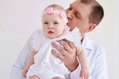 Father kissing his daughter. Close-up shot of a father holding and kissing his daughter. Girl wearing beautiful white dress; looking aside Stock Image