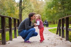 Father kissing his little daughter in a park. This image has attached release Royalty Free Stock Photos