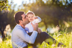 Father kissing his little son, sitting on the grass Royalty Free Stock Photography