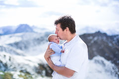 Father kissing his newborn baby son in mountains. Young father kissing his newborn baby son with beautiful snow covered mountains in the background royalty free stock photography