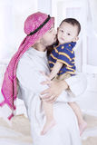 Father kissing his son in bedroom. Arabian men kissing his son while standing in the bedroom with islamic clothes stock images