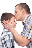 Father kissing his son on the forehead. Isolated on white stock photos