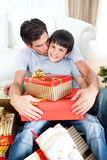 Father kissing his son after giving him a present. Father kissing his son after giving him a Christmas gift in the living-room Stock Image