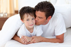 Father kissing his son lying on bed. Happy Father kissing his son lying on bed Stock Photos