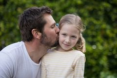 Father kissing his young girl. In the park Stock Images