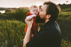 Father kissing infant baby outdoor Fathers day. Holiday happy family lifestyle dad and daughter child walking together summer vacations parenthood concept stock photography