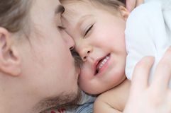 Father kissing little baby daughter and putting her to sleep stock photos