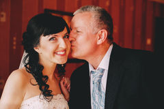 Father kissing smiling bride Stock Photos