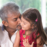 Father kissing toddler daughter. Happy Indian family at home. Asian dad kissing his toddler. Father and daughter indoor lifestyle Royalty Free Stock Photography