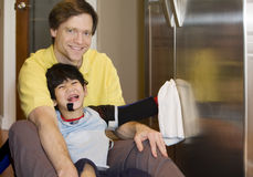Father on kitchen floor with disabled son. Cleaning the fridge. Son has cerebral palsy, with leg orthotics and arm splints Stock Photos