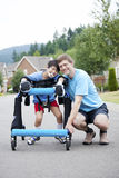 Father kneeling next to disabled son in walker royalty free stock image