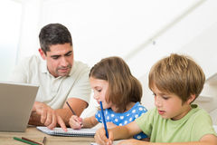 Father with laptop assisting children drawing Stock Image