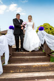 Father leading happy bride to wedding altar down the stairs Stock Photo