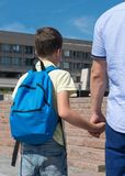 Father leads a child to school on classes holds his hand stock photo