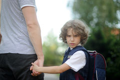 The father leads by the hand in school of the little schoolboy. The boy turned around and looked at the camera with an angry expression. The student does not Royalty Free Stock Image