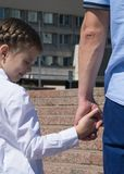 Father leads his daughter`s hand to school, close-up stock photography