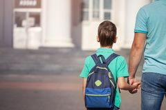 Father leads a little child school boy go hand in hand. Parent and son with backpack behind the back.  royalty free stock photography