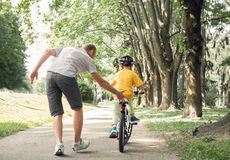 Father learn his little son to ride a bicycle Stock Images