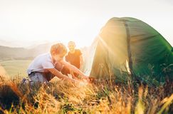 Father learn his son set up camping tent on sunset forest glade stock image