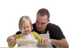 Father learning his little girl how to make a cake Stock Image