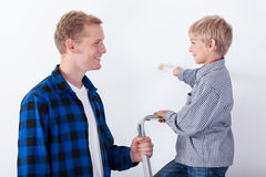 Father learning his son painting a wall Stock Photos