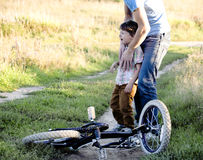 Father learning his son to ride on bicycle outside in green park, falling hurt, crying kid Stock Photo