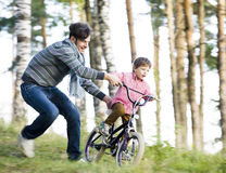 Father learning his son to ride on bicycle outside in green park, real happy family, lifestyle people concept Stock Photo