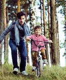 Father learning his son to ride on bicycle outside in park Stock Photography