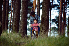 Father learning his son to ride on bicycle outside Royalty Free Stock Photo