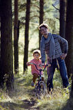 Father learning his son to ride on bicycle outside Royalty Free Stock Image