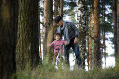 Father learning his son to ride on bicycle outside, real happy family in summer forest enjoing nature Royalty Free Stock Images